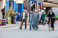 Essaouira, Morocco.  Men Walking, Cycling in Avenue de l'Istiqlal.  Traditional vs. Western Clothing Styles.
