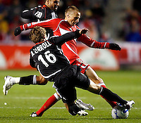 DC United midfielder Brian Carroll (16) slide tackles the ball away from Chicago Fire forward Chris Rolfe (17). The Chicago Fire defeated D. C. United 1-0 during the first leg of the MLS Eastern Conference Semifinal Series at Toyota Park in Bridgeview, IL, on October 25, 2007.