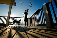 A teenage boy feeds the sea birds on Dauphin Island, Alabama, a barrier island located three miles south of the mouth of Mobile Bay in the Gulf of Mexico. This island, which is approximately 14 miles long and less than two miles wide, appears to have fully recovered from the impact of Hurricane Katrina (2005) and the BP Deepwater Horizon Oil Spill in 2010. Both events greatly reduced tourism income (fewer people came to the island) and local business owners say many establishments went out of business. Today they say they're looking forward to a rebounding tourism business.