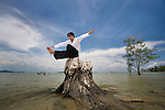 A man stretches and does yoga on a tree stump on a beach in Koh Lanta, Thailand.