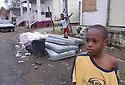 Nine-year-old Dejean Lawless and his cousins play in the debris in their 7th Ward neighborhood in New Orleans, Fri., Jan. 19, 2007.