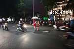Ha and Xo cross a street at night in Hue, Vietnam. Dec. 27, 2012.