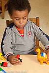 Preschool 3-4 year olds boy playing with plastic human figures and toy animals talking to himself