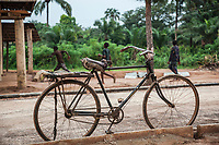 Nigeria. Enugu State. Owo. Outside Saint Mary's Catholic Parish. An old bicycles parked on the sidewalk, Three young black boys are running in the background  9.07.19 © 2019 Didier Ruef