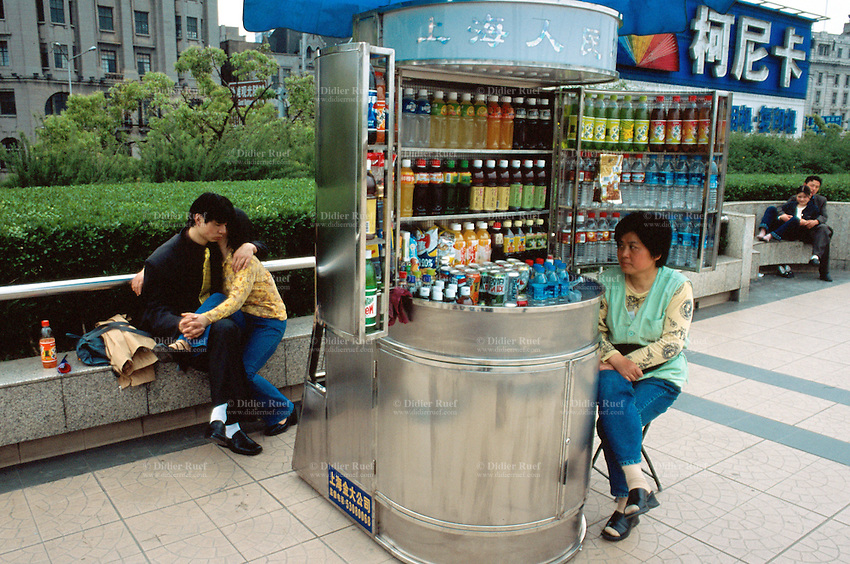 """China. Shanghai.  """"The Bund"""". Late afternoon, lovers enjoying passionate and tender moments near a small shop which sells various soft drinks and water bottles. The Bund is the most impressive 2 km in Shanghai.  © 2002 Didier Ruef"""