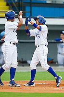 Ramon Torres (25) of the Burlington Royals is congratulated at home plate by teammate Alfredo Escalera-Maldonado (21) after hitting a home run against the Pulaski Mariners at Burlington Athletic Park on July 20, 2013 in Burlington, North Carolina.  The Royals defeated the Mariners 6-5.  (Brian Westerholt/Four Seam Images)