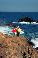Middle-aged couple walking along a rocky coastline.