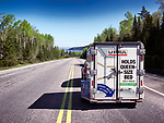 Rear view of a car with a rental U-Haul UHAUL cargo trailer driving on a highway, moving and transportation concept. Trans-Canada Highway, Ontario, Canada.