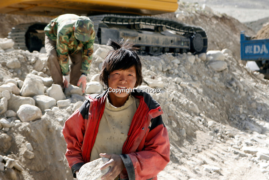"""A young boy carries rocks to build the road to Mt Everest.<br /> China started building a controversial 67-mile """"paved highway fenced with undulating guardrails"""" to Mount Qomolangma, known in the west as Mount Everest, to help facilitate next year's Olympic Games torch relay.<br /> Tibet, China<br /> July, 2007"""