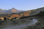 Silver SUV on dirt road with Mount Sneffels (14,150 ft) behind, autumn, Colorado.