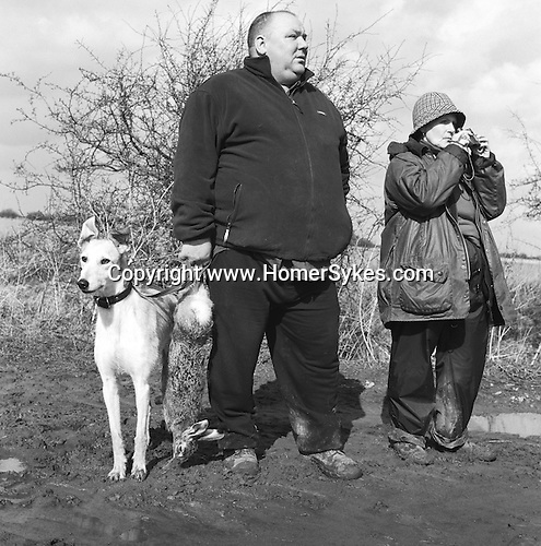 Rat and Rabbit and Lurcherwork...Single handed Hare Coursing for Hare and Rabbit...John Armstrong from the North East Lurcher Club a guest of The Old English and Colonial Lurcher Club hunting in Lincolnshire on an extremely cold and blustery February day.  Barbara Tyer wraps up to keep the wind and rain out....Hunting with Hounds / Mansion Editions (isbn 0-9542233-1-4) copyright Homer Sykes. +44 (0) 20-8542-7083. < www.mansioneditions.com >..