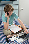 15 year old boy doing homework in bedroom using computer and cell phone