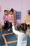 Education preschool child care program 3-4 year olds 3 girls playing game with blocks they laid out in a grid