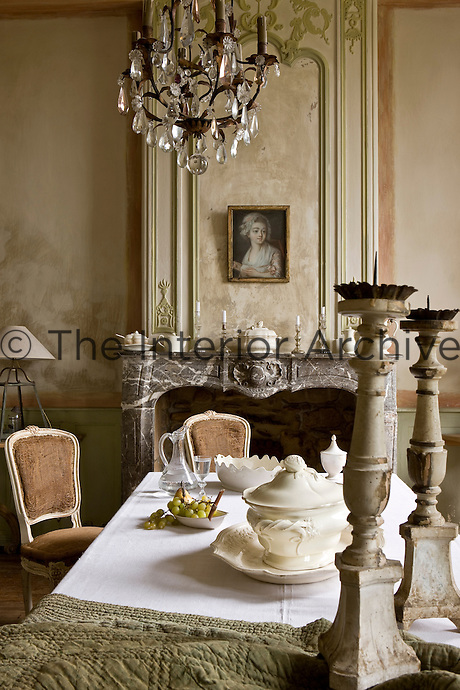 A collection of fine English and French creamware is displayed on the table and mantelpiece in the dining room