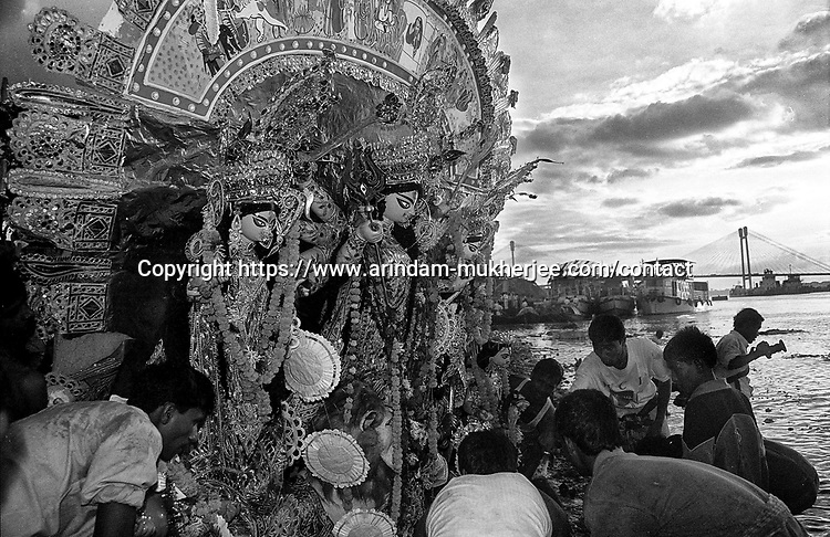Durga idol is being taken for immerssion on the last day of the festival. Its a ritual of drowning the idol in the Ganges after the worship is over. Durga Puja Festival is the biggest festival among bengalies.  As Calcutta is the capital of West Bengal and cultural hub of  the bengali community Durga puja is held with the maximum pomp and vigour. Ritualistic worship, food, drink, new clothes, visiting friends and relatives places and merryment is a part of it. In this festival the hindus worship a ten handed godess riding on a lion armed wth all possible deadly ancient weapons along with her 4 children (Ganesha - God for sucess, Saraswati - Goddess for arts and education, Laxmi - Goddess of wealth and prosperity, Kartikeya - The god of manly hood and beauty). Durga is symbolised as the women power in Indian Mythology.  In Calcutta people from all the religions enjoy these four days of festival in the moth of October. Now the religious festival has become the biggest cultural extravagenza of Calcutta the cultural capital of India. Artistry and craftsmanship can be seen in different sizes and shapes in form of the idol, the interior decor and as well as the pandals erected on the streets, roads and  parks.- Arindam Mukherjee
