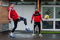 SWANSEA, WALES - JANUARY 28:  Angel Rangel of Swansea City and Jordi Amat of Swansea City play around with the ball outside the training ground  on January 28, 2015 in Swansea, Wales.