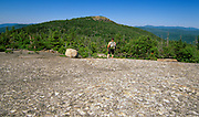 Hiker on Davis Path, with Mount Crawford in the background, in the White Mountains, New Hampshire.