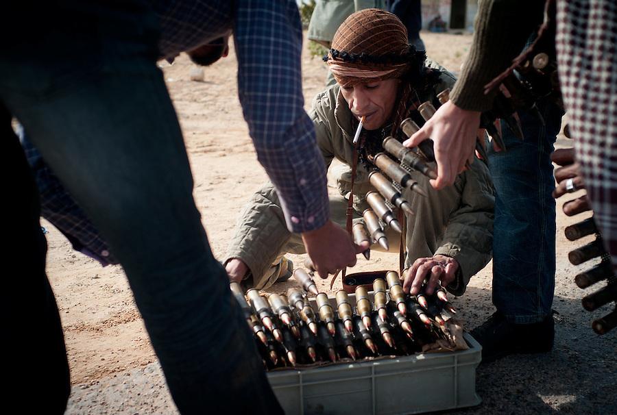 Rebel fighters prepare bullets outside of Ajdabiya, Libya.