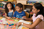 Education Elementary School Kindergarten mathematics using manipulatives, boy and girl working with teacher