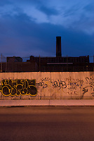 Williamsburg, Brooklyn, New York City, New York State, USA....Street, Sidewalk, Wall with Graffiti, and the landmarked former Domino Sugar Refinery in the Distance