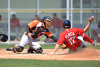 Baltimore Orioles catcher Geremias Gil (74) blocks the plate as Michael Flacco (17) slides in during a minor league Spring Training game against the Boston Red Sox at Buck O'Neil Complex on March 25, 2013 in Sarasota, Florida.  (Mike Janes/Four Seam Images)