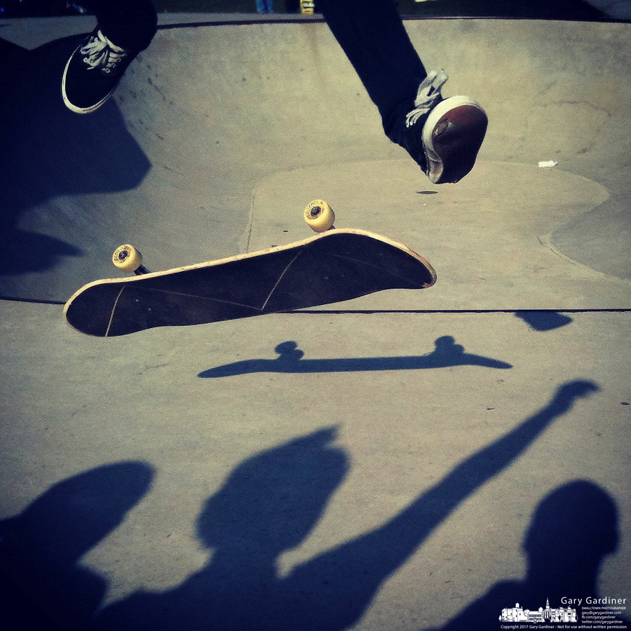 Skateboarder in mid-trick as other's shadows are cast across concrete at Halloween skateboarding event at Westerville Skate Park.