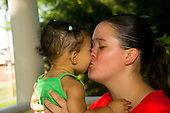 MR / Schenectady, NY. Mother (20) and infant daughter (girl, 9 months, African American & Caucasian) kiss. MR: Dal4, Dal6. ID: AL-HD. © Ellen B. Senisi