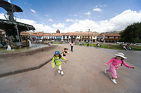 YOUNG PERUVIAN GIRLS PLAYING IN FRONT OF THE WATER FOUNTAIN AT PLAZA DE ARMAS, CUZCO, PERU