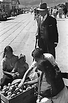 San Cristobal de las Casas 1970s Mexico. Elderly man has servant  to buy fruit for him from Indigenous young Indian girls with a baby selling in the daily market. 1973 Mexican State of Chipas.