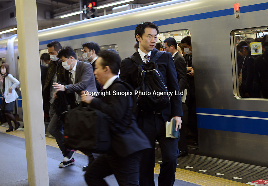 Businessmen rush for trains during the early morning commute, shinjuku Station, Tokyo. With up to 4 million passengers passing through it every day, Shinjuku station, Tokyo, Japan, is the busiest train station in the world. The station was used by an average of 3.64 million people per day.  That's 1.3 billion a year.  Or a fifth of humanity. Shinjuku has 36 platforms, and connects 12 different subway and railway lines.  Morning rush hour is pandemonium with all trains 200% full. <br /> <br /> Photo by Richard jones / sinopix