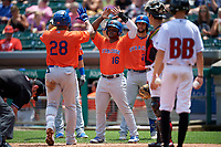 Syracuse Mets Rymer Liriano (28) is congratulated by teammates Dilson Herrera (16), Colton Plaia (24) after hitting a home run during an International League game against the Indianapolis Indians on July 17, 2019 at Victory Field in Indianapolis, Indiana.  Syracuse defeated Indianapolis 15-5  (Mike Janes/Four Seam Images)