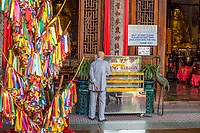 Kek Lok Si Buddhist Temple, Man Examining Wishing Ribbons for Good Luck, Happiness, and Success.  Wishing Ribbon Tree on Left. George Town, Penang, Malaysia.