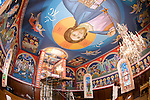 Main Byzantine Pantocrator  of Christ looms over the ceiling created Miloje Milinkovic iconographer inside St. Sava Serbian Orthodox Church, Jackson, Calif. Assistant Slobodan Kikovich paints the border below.
