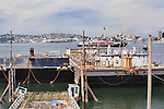 Seattle Skyline from Harbor Island industrial area viewed over idle oil barges, unused rail terminal, and anchored barges.