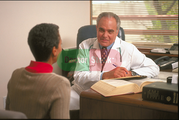 male doctor explaining diagnosis to female patient in doctor's office