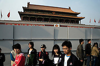 Tourists walk past construction outside the Tiananmen Gate of the Forbidden City compound in Beijing, China.