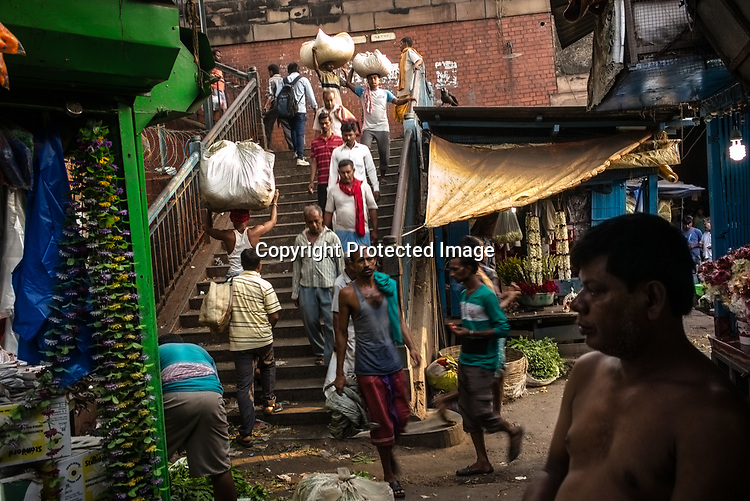 Pedestrians walk down the steps from the Howrah bridge to the Mullik Ghat flower market in Howrah, Kolkata, West Bengal  on Friday, May 26, 2017. Photographer: Sanjit Das