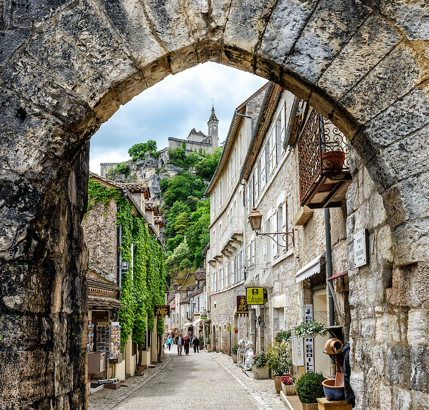 View of the main street in Rocamadour through the Porte du Figuier, a 13th century archway.