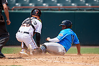 Akron RubberDucks Wilson Garcia (11) slides home safely as the ball got away from catcher Brett Cumberland (28) during an Eastern League game against the Bowie Baysox on May 30, 2019 at Prince George's Stadium in Bowie, Maryland.  Akron defeated Bowie 9-5.  (Mike Janes/Four Seam Images)