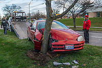 Tow truck drivers remove a car from the median on Huber Village after it struck a tree when hit by another car.
