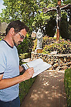 Young man draws setting with crown of thorns bush around the station of the cross at the San Gabriel Mission field trip to inform for design class what makes it sacred.