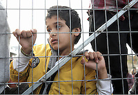 Pictured: A young child watches on through the camp fence Monday 06 February 2017<br /> Re: Scuffles between migrants and police broke out during a visit by Immigration Policy Minister Yiannis Mouzalas at the Elliniko migrant camp located in the former airport in the outskirts of Athens, Greece.