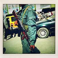An Afghan policeman carrying an AK47 rifle patrols a busy street.