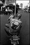 Summer '99-- Jakarta, Indonesia -- A supporter of Megawati holds a party flag on  the back of a motorcycle after a political rally. Political life is tough on the world's most inhabited island in the world's biggest muslim nation.