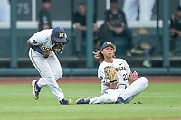 Michigan Wolverines outfielder Jordan Brewer (22) makes a sliding catch while avoiding second baseman Ako Thomas (4) against the Vanderbilt Commodores during Game 2 of the NCAA College World Series Finals on June 25, 2019 at TD Ameritrade Park in Omaha, Nebraska. Vanderbilt defeated Michigan 4-1. (Andrew Woolley/Four Seam Images)