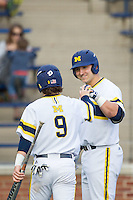 Michigan Wolverines catcher Harrison Wenson (7) greets teammate Michael Brdar (9) after he scored against the Eastern Michigan Hurons on May 3, 2016 at Ray Fisher Stadium in Ann Arbor, Michigan. Michigan defeated Eastern Michigan 12-4. (Andrew Woolley/Four Seam Images)