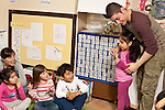 Education Preschool Headstart 3-4 year olds counting activity at circle time with young male teacher