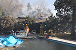 Firefighters work to protect a home in the path of a 400-acre brush fire in Reno, Nev., on Friday, Nov. 18, 2011. More than 25 homes have been lost as high winds with gusts up to 60 mph drive the flames.  (AP Photo/Cathleen Allison)