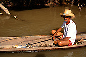 Pantanal, Mato Grosso State, Brazil; old man wearing a straw hat in a dugout canoe with fish in the bottom.