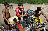 Smugglers push bicycles loaded with gasoline barrels on the shore of the river Tachira on the Colombia-Venezuela border, 2 May 2006. Venezuelan gasoline, being 20 times cheaper than in Colombia, is the most wanted smuggling item, followed by food and car parts, while reputable Colombian clothing flow to Venezuela. There are about 25,000 barrels of gasoline crossing illegally the Venezuelan border every day. The risky contraband smuggling, especially during the rainy season when the river rises, makes a living to hundreds of poor families in communities on both sides of the frontier.